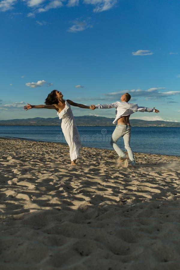 Танцы человека и женщины, пара счастливая на каникулах Соедините в любов бежать на пляже, seashore Пара в любов держит руки стоковое фото