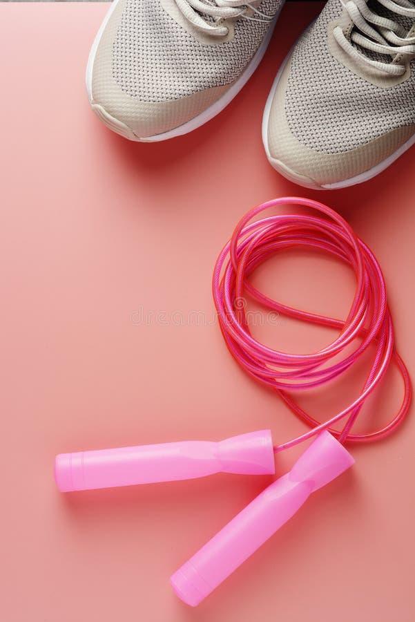 Тапки, ботинки спорта и скача веревочка над розовой предпосылкой Здоровье, идущая концепция разминки, фитнеса и йоги Женственный стоковые фото