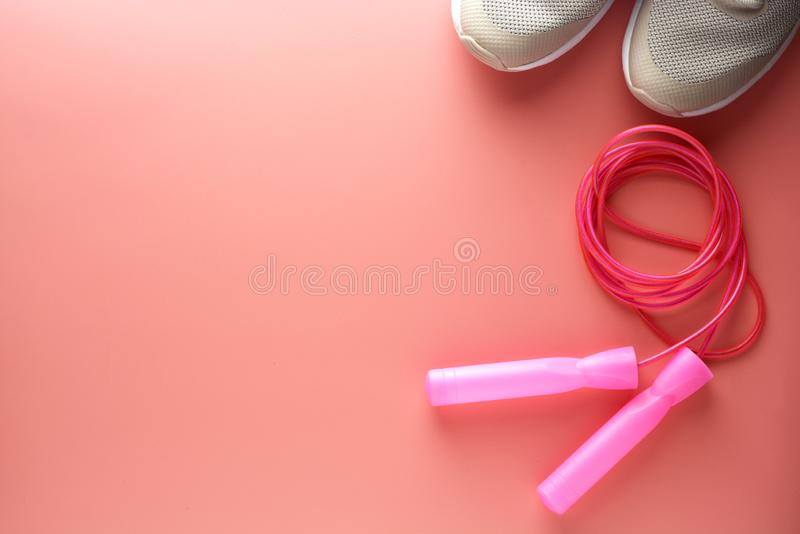 Тапки, ботинки спорта и скача веревочка над розовой предпосылкой Здоровье, идущая концепция разминки, фитнеса и йоги Женственный стоковое изображение rf