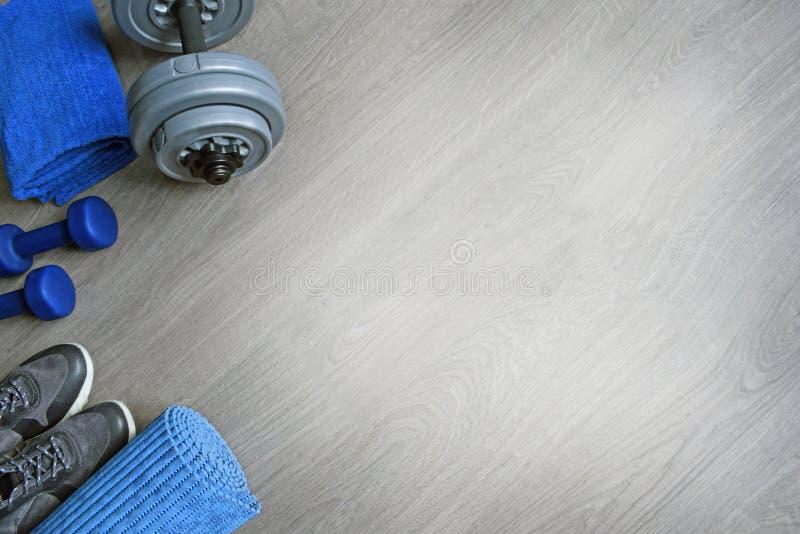 Тапки, 2 голубых гантели, полотенце и циновка разминки стоковые фото