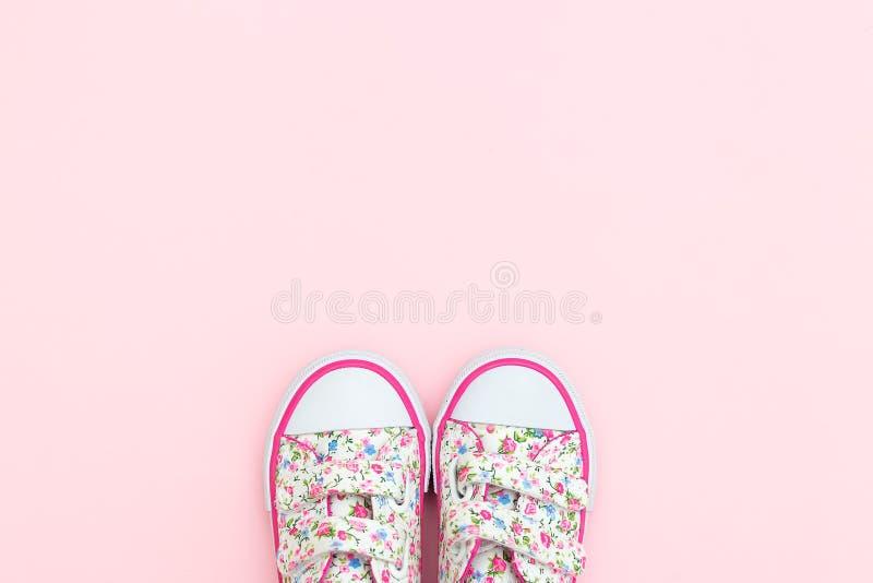 Тапки для маленькой девочки в цветках и розовый цвет на пастельном b стоковые фото