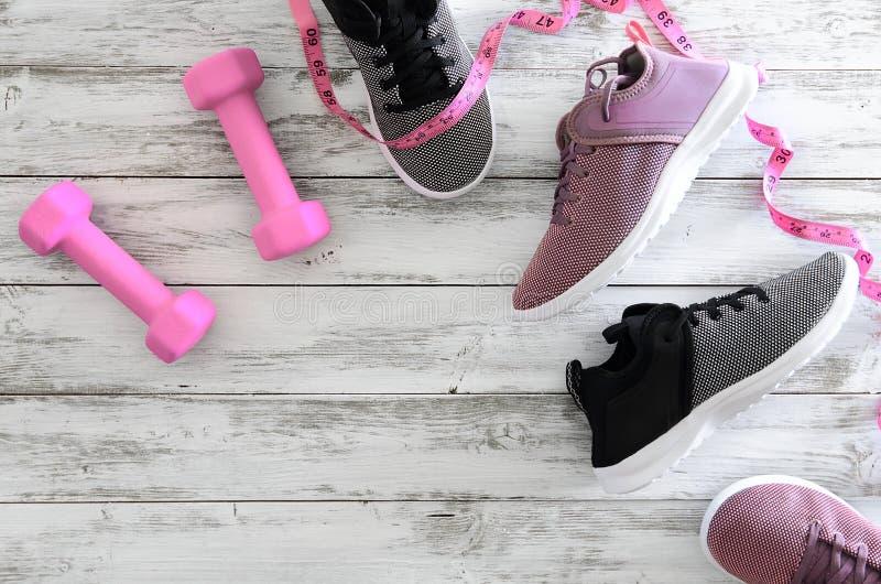 Тапки обуви спорта женщин и гантели оборудования розовые, стоковая фотография