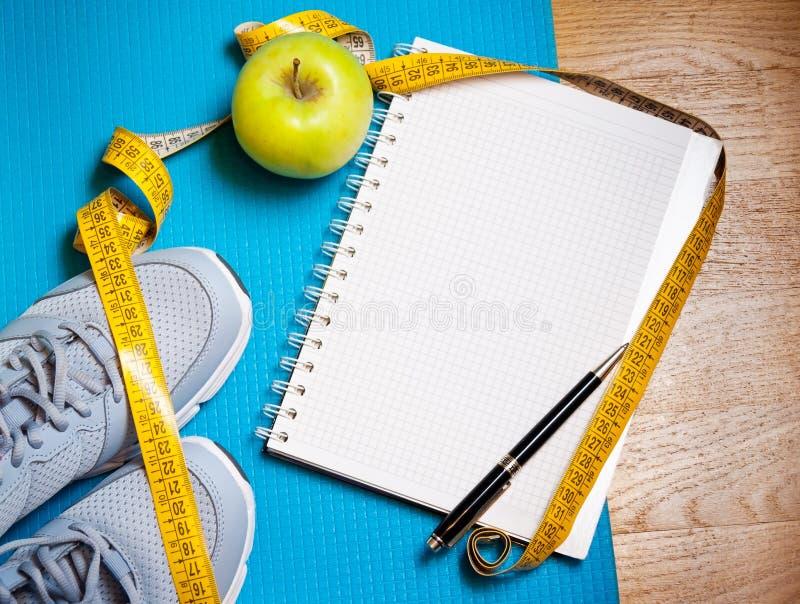 Тапки, сантиметр, зеленое яблоко, тетрадь красивейшая потеря принципиальной схемы живота над женщиной веса белой стоковые изображения