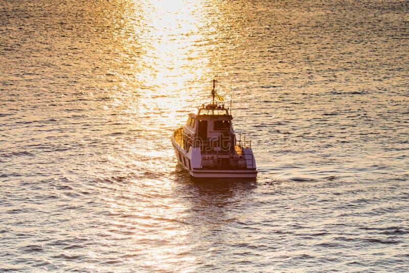 Таранто, Apulia/Италия - 03/25/2019: Шлюпка службы береговой охраны защищает побережье Таранта на заходе солнца на теплом после п стоковые изображения