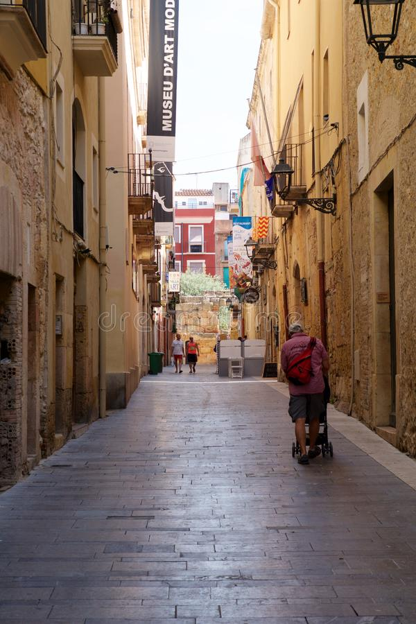 ТАРРАГОНА, ИСПАНИЯ - 28-ое августа 2017: Дезертированная улица старого европейского городка на ясный солнечный день Яркие стены  стоковые фото