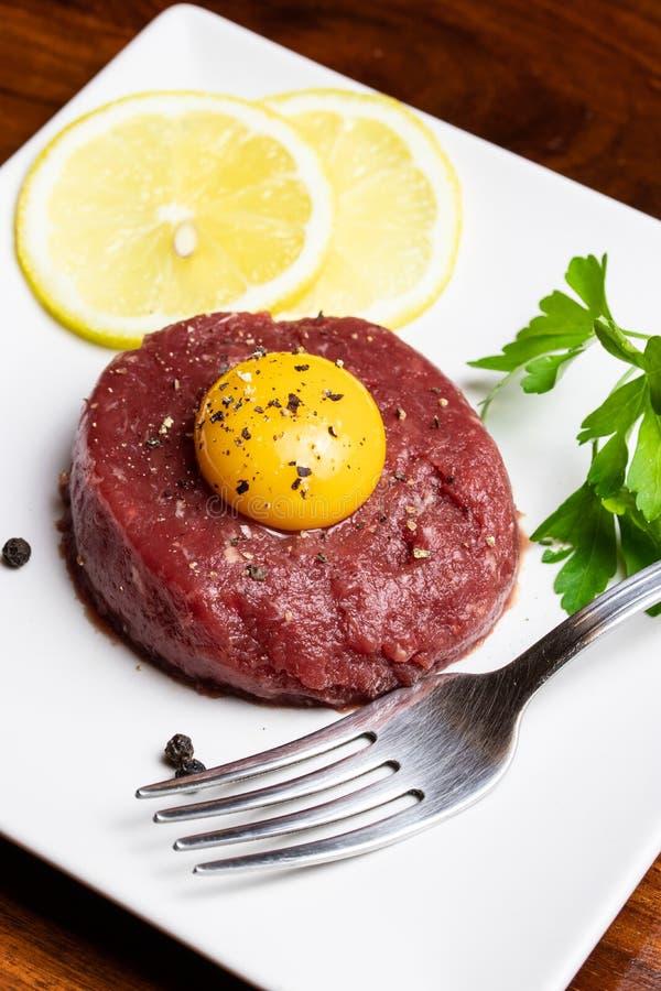 Тартар из говядины с яичным желтком на белой плите стоковые фотографии rf