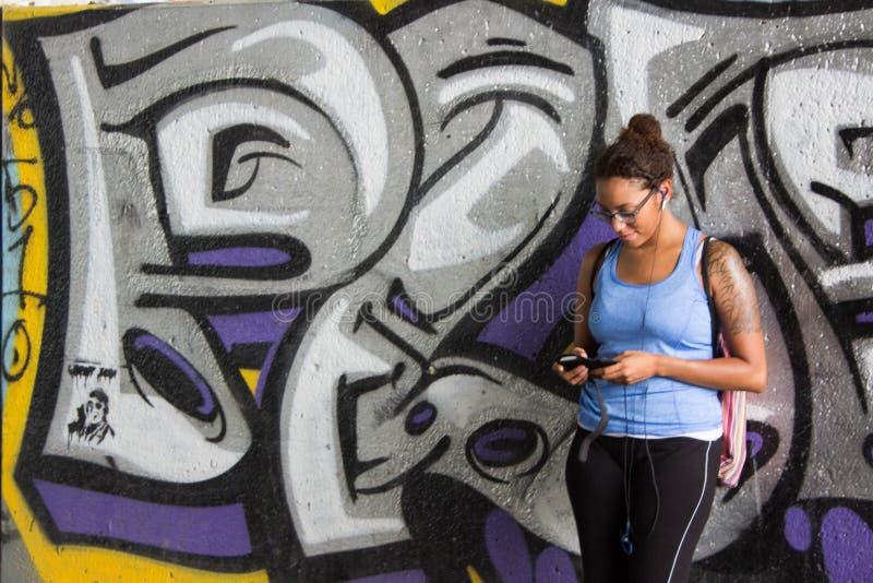 Татуированная девушка в склонности на стене граффити стоковое изображение rf