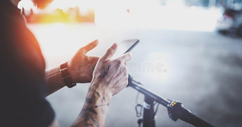 Татуированный мышечный мобильный телефон удерживания мужчины в руках и использовании приложения карты для подготовки маршрута дор стоковое изображение