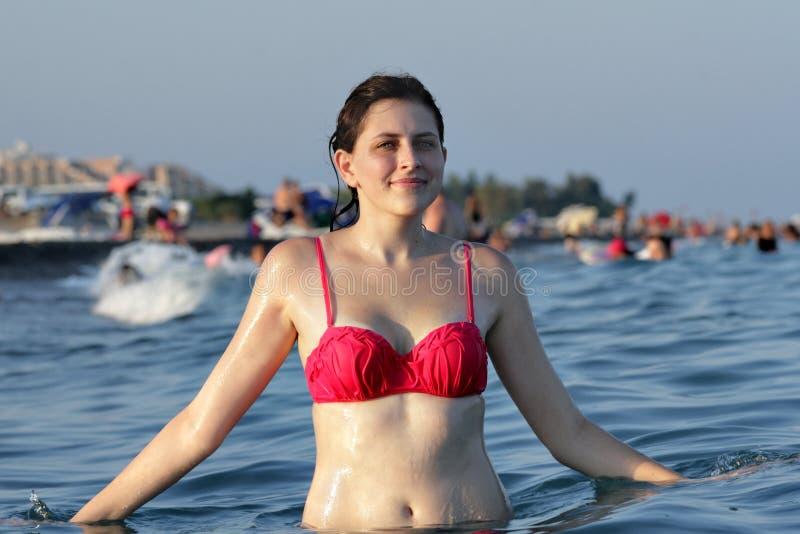 Талия молодой женщины стоящая глубоко в воде, на предпосылке пляжа стоковая фотография rf