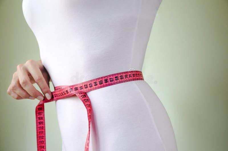 Талия худенькой женщины в белом нижнем белье с измеряя лентой стоковая фотография rf