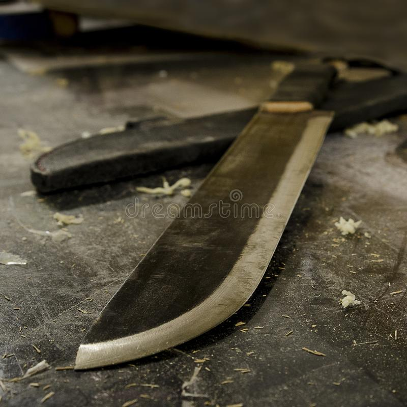 Твердое стальное ручной работы мачете на работая столе стоковое изображение rf