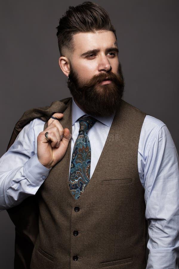 Твердый человек с бородой и усик в классическом модном костюме стоковое фото