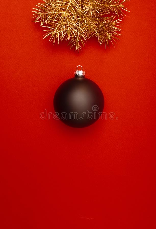 Творческая вертикальная картина с золотыми ветвями рождественской елки и большой черной безделушкой Концепция стоковые фотографии rf