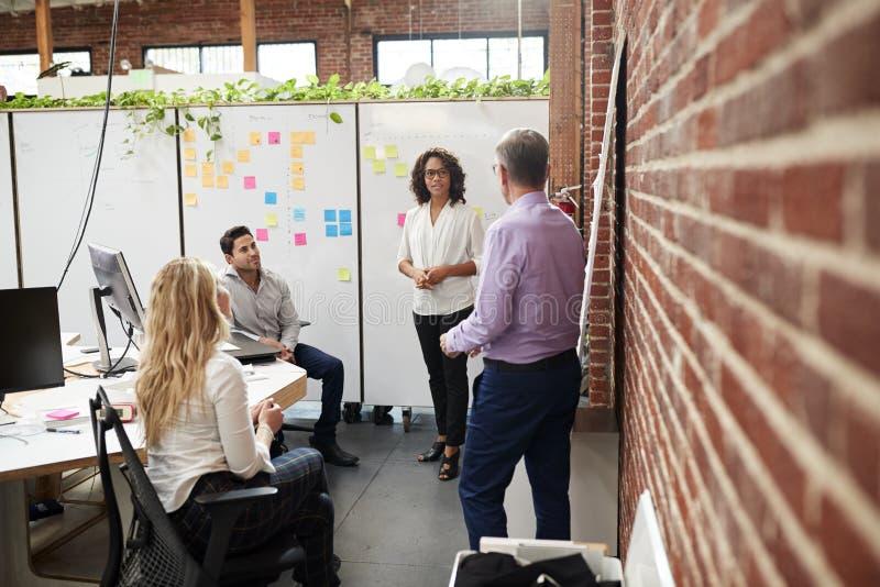 Творческая встреча команды для того чтобы обсудить идеи в современном офисе стоковое фото