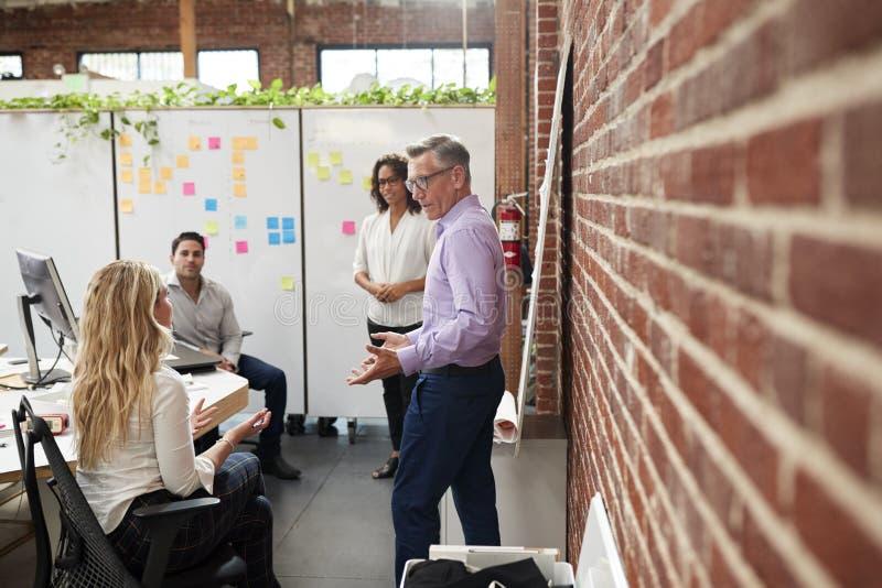 Творческая встреча команды для того чтобы обсудить идеи в современном офисе стоковое фото rf