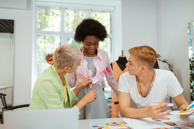 Творческая команда профессиональных модельеров сидя внутри помещения стоковая фотография