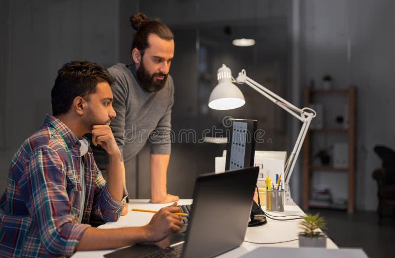 Творческая команда с деятельностью компьютера поздно на офисе стоковое изображение