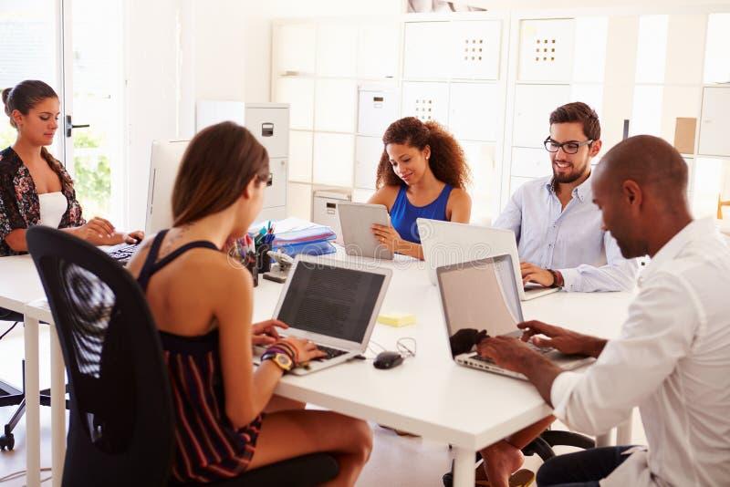 Творческая команда работая в офисе начинает вверх дело стоковые фото