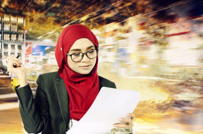 Творческая концепция идей, успешные молодые коммерсантки muslimah читая что-то на бумаге над абстрактным backgroun двойной экспоз стоковая фотография rf