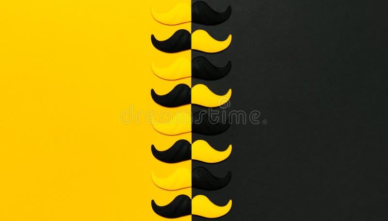 Творческая концепция украшения партии Черный и желтый усик, упорки для будочек фото, партий масленицы на черной желтой предпосылк стоковое фото