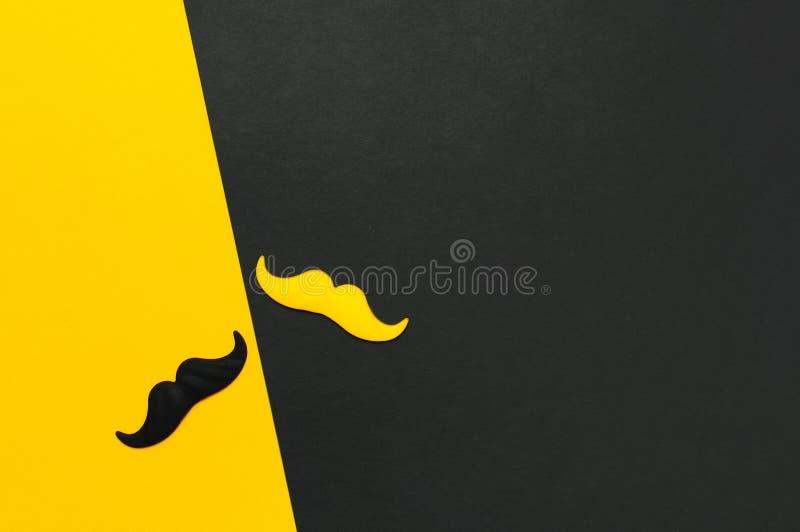 Творческая концепция украшения партии Черный и желтый усик, упорки для будочек фото, партий масленицы на черной желтой предпосылк стоковые фото