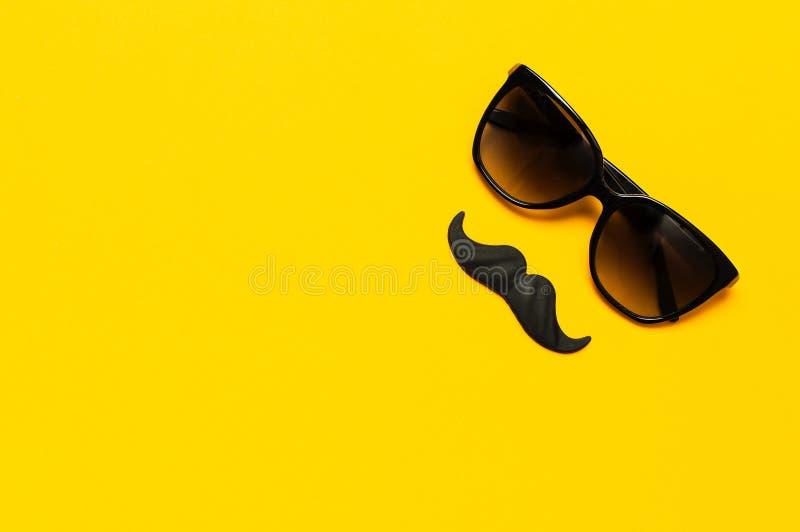 Творческая концепция украшения партии Черный усик, солнечные очки, упорки для будочек фото, партий масленицы на желтой верхней ча стоковые фото