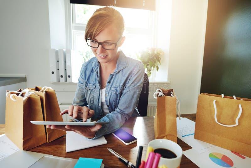 Творческая молодая женщина с ее собственным e-делом стоковые фото