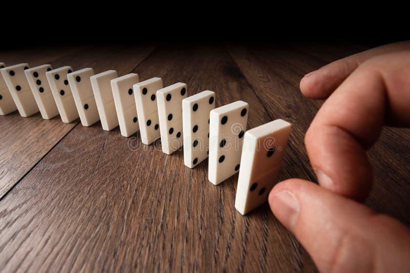Творческая предпосылка, мужская рука нажимая белые домино, на коричневой деревянной предпосылке Концепция эффекта домино, цепи стоковая фотография