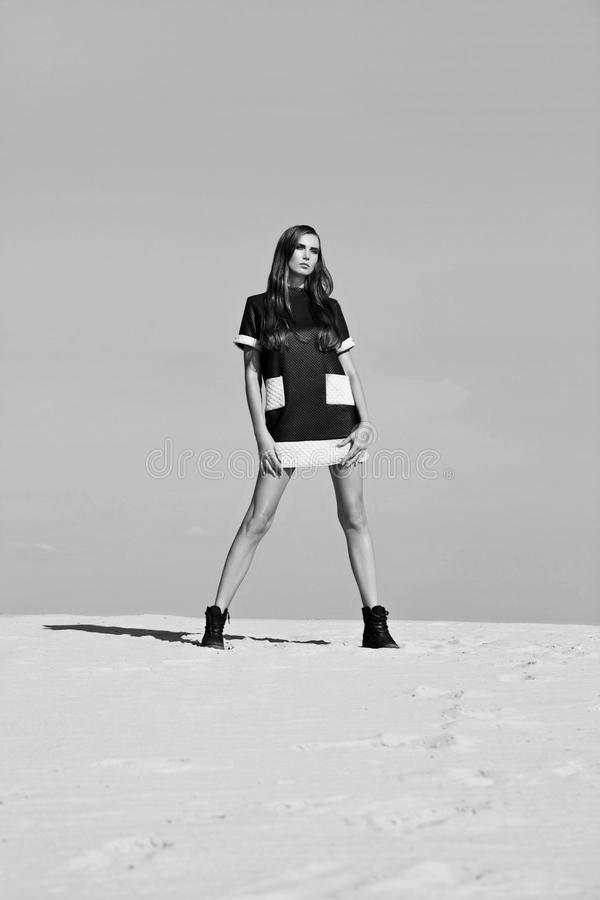 Творческая съемка в пустыне Красивая сексуальная девушка в черном платье T стоковое изображение