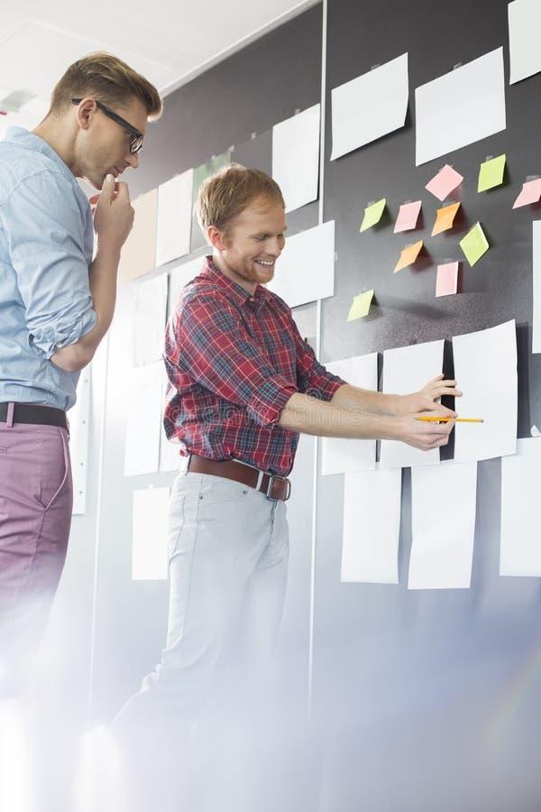 Творческие бизнесмены обсуждая над документом на стене в офисе стоковое изображение