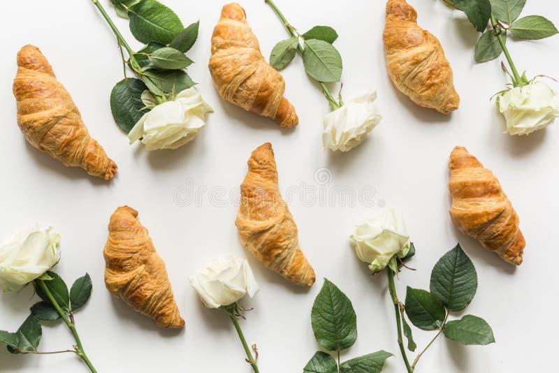 Творческие еда и цветочный узор свежо круассанов и белых роз r стоковые изображения