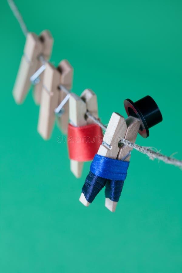 Творческие характеры и веревка для белья колышка дизайна Человек в костюме, платье женщины красном деревянные зажимки для белья н стоковые изображения rf