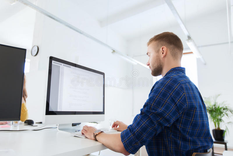 Творческие человек или программист с компьютером на офисе стоковые изображения