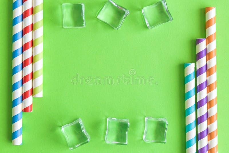 Творческий конспект состава предпосылки лета с выпивая соломами и кубами льда изолированными на зеленом цвете r стоковое изображение