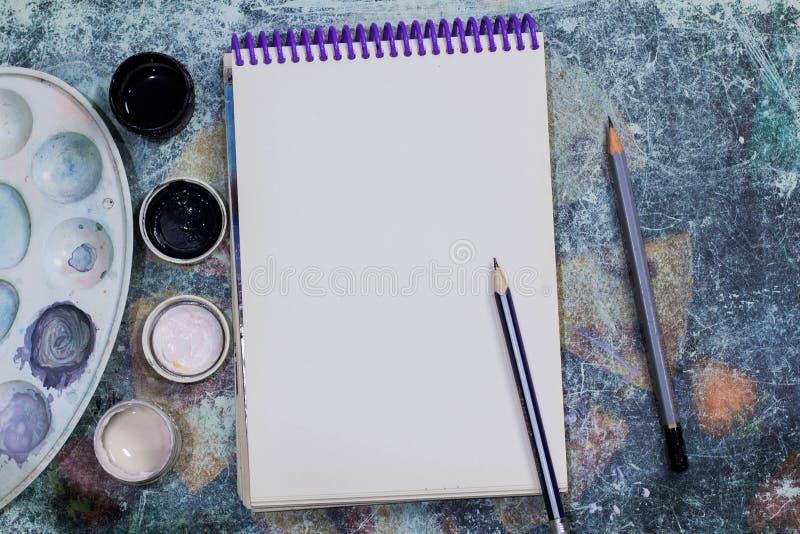 Творческий космос Рабочая зона художника на затрапезной таблице: покрасьте гуашь, тетрадь, карандаши стоковые фотографии rf