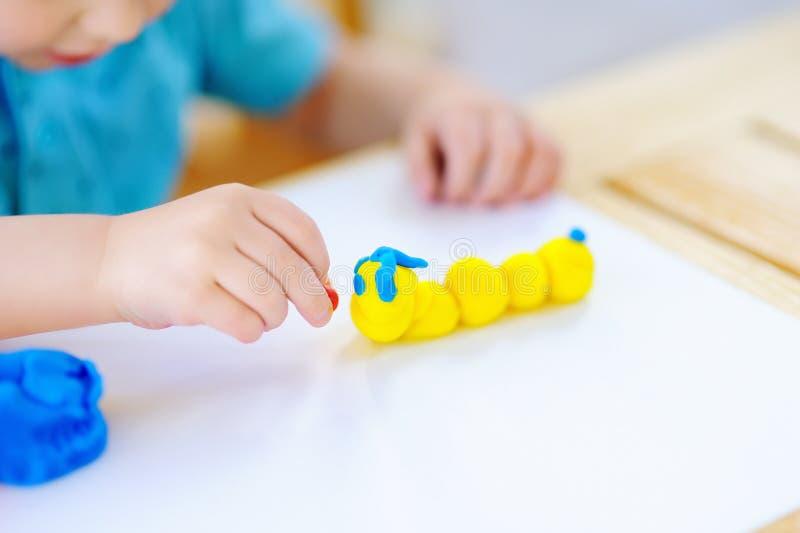 Творческий мальчик играя с красочной глиной моделирования на детском саде стоковая фотография rf