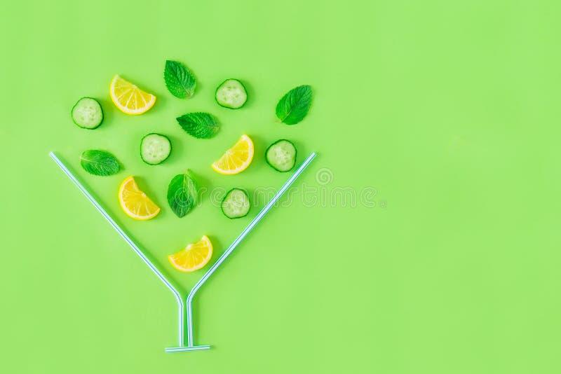 Творческий план ингридиентов лимонада - лимон, мята, огурец отрезает падать в стекло coctail сделанное с соломами на зеленом back стоковая фотография