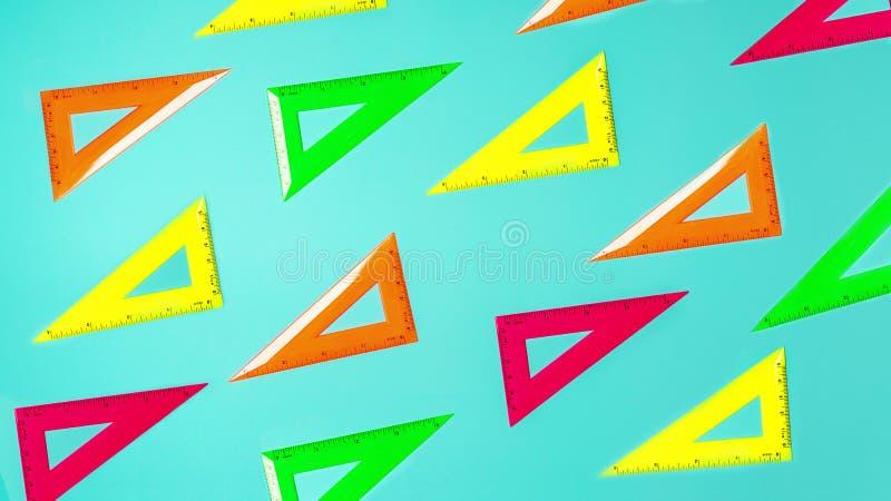 Творческий план картины правителей неоновых цветов школьных принадлежностей квадратной против пастельной голубой предпосылки стоковые фото