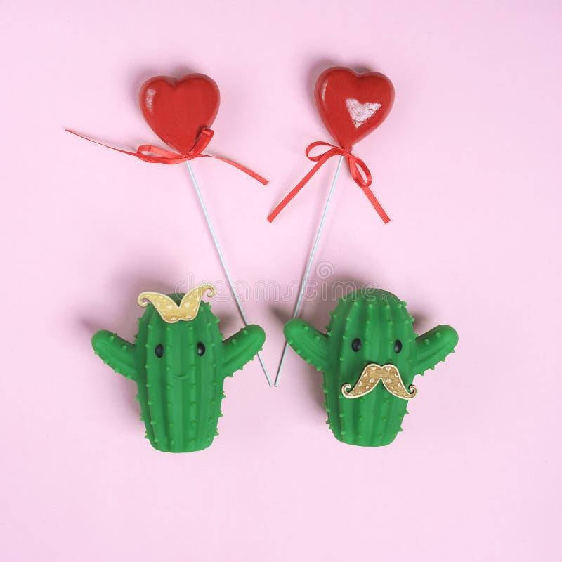 Творческий смешной кактус дизайна дня Валентайн женский со смычком и мужчиной с усиком и красными сердцами на розовой предпосылке стоковая фотография