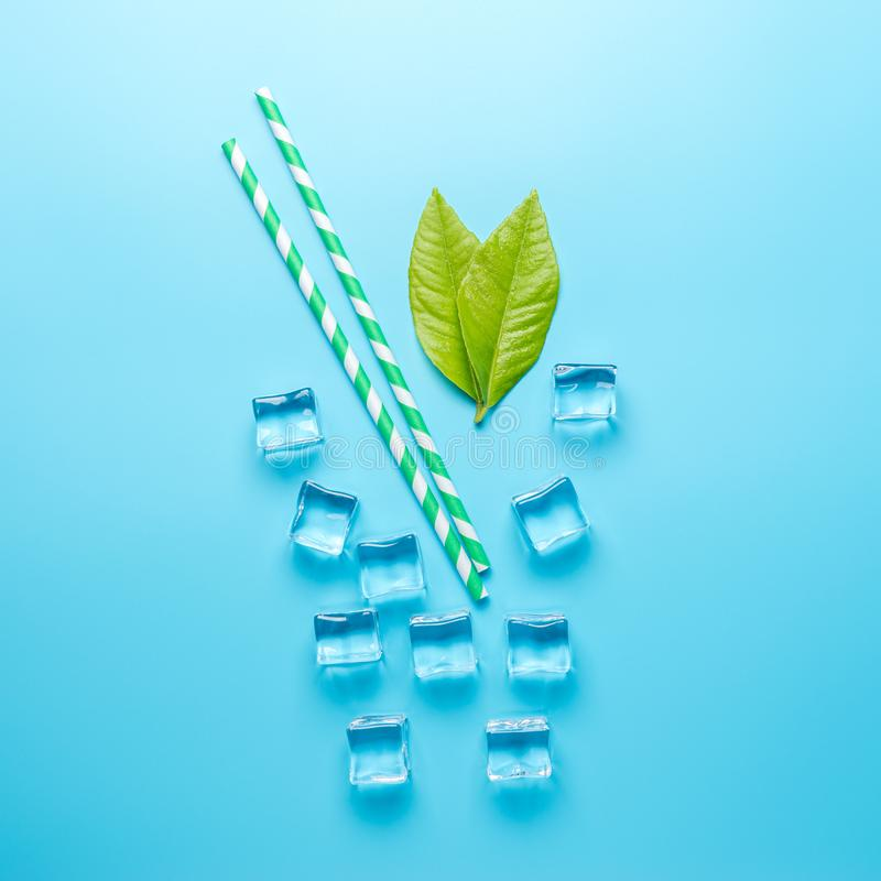 Творческий состав лета с кубами соломы и льда на голубой предпосылке Минимальная концепция напитка стоковое фото