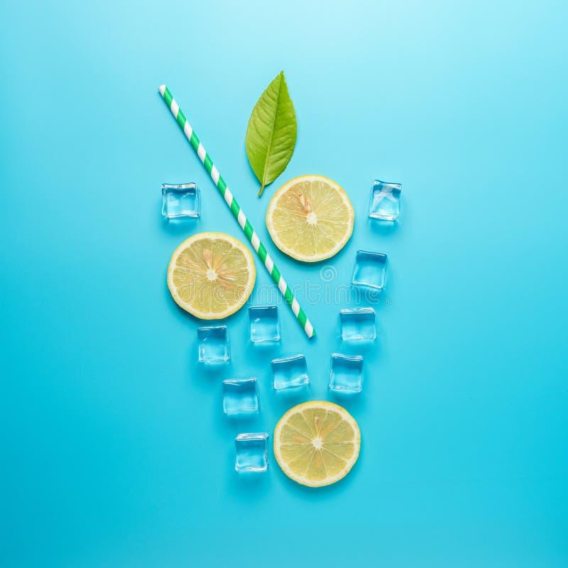 Творческий состав лета с отрезанными кубами лимона, соломы и льда на голубой предпосылке Минимальная концепция напитка стоковое изображение
