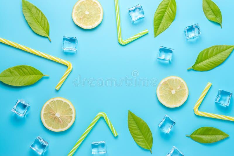 Творческий состав лета с отрезанными кубами лимона, соломы и льда на голубой предпосылке Минимальная концепция напитка стоковые фото