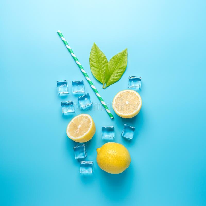 Творческий состав лета с отрезанными кубами лимона, соломы и льда на голубой предпосылке Минимальная концепция напитка стоковое фото