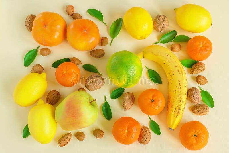 Творческий состав разнообразие плодов Сочный свежий цитрус, Яблоко, банан, хурма, гайки и зеленые листья на свете стоковая фотография