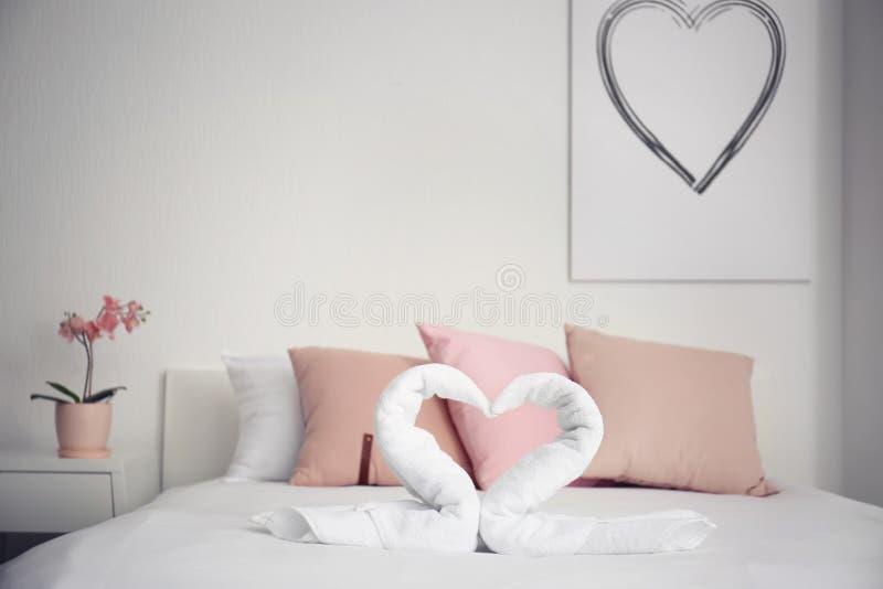 Творческий состав с лебедями сделанными из белых полотенец Terry на кровати внутри помещения стоковое фото