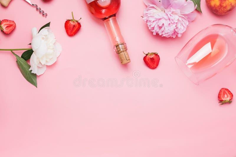 Творческий состав с розовым вином и очень вкусными клубниками на розовой предпосылке стоковая фотография