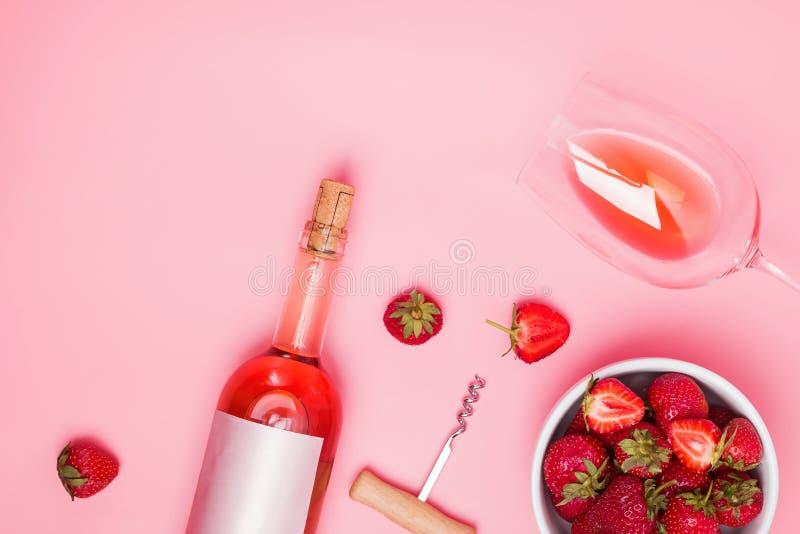 Творческий состав с розовым вином и очень вкусными клубниками на розовой предпосылке стоковые фото