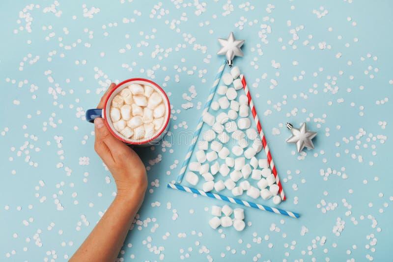 Творческий состав с чашкой владением руки женщины горячих какао или шоколада и ели рождества сделанной из зефира на голубом столе стоковые фотографии rf