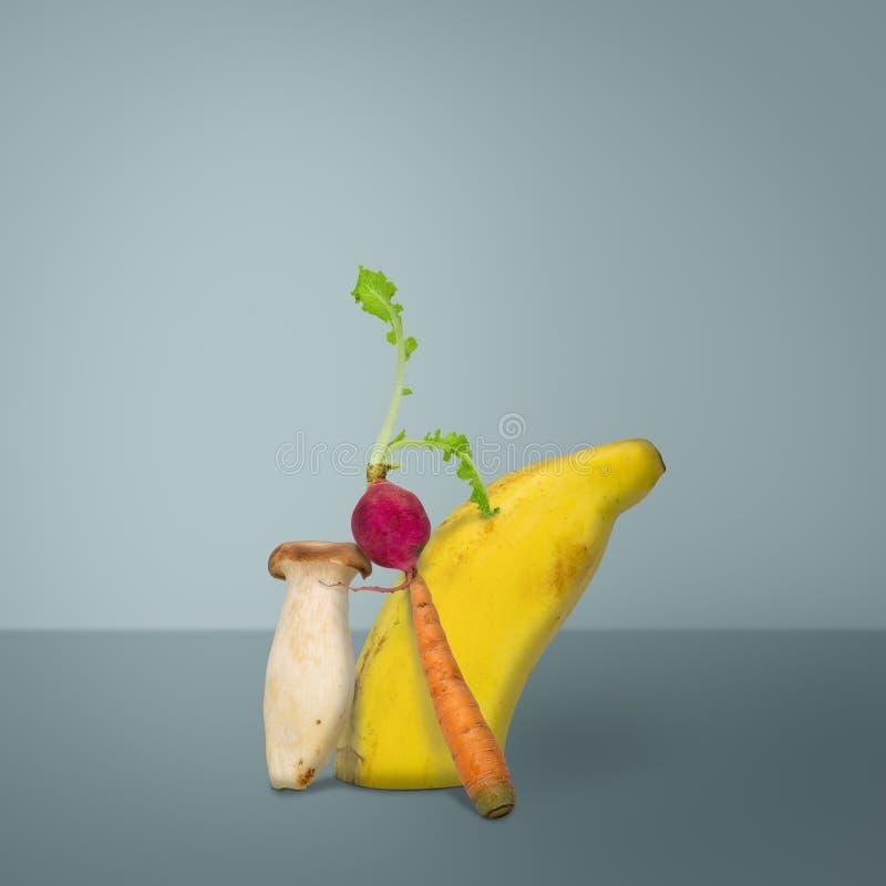 Творческий фруктов и овощей банан, редиска, гриб, и морковь, на голубой предпосылке стоковая фотография