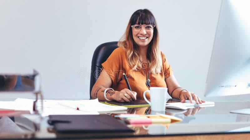 Творческий художник на работе сидя на ее столе стоковая фотография rf
